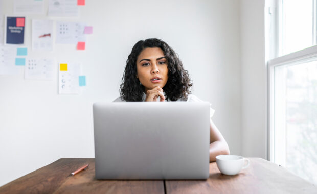 Woman sitting at her laptop looking pensive
