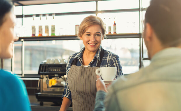 Barista smiling while serving white coffee cup to customer's hand.